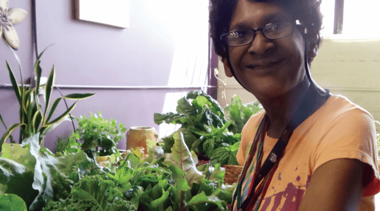 Woman of color wearing an orange shirt and smiling while standing next to plants