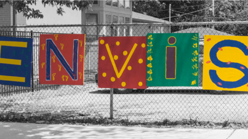 "Colorful painted sign saying, ""Envision"" hanging outside on a fence on a snowy day"