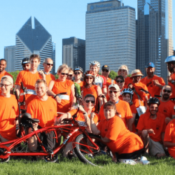 "Large group photo outdoors with cityline in the background while wearing orange ""Bike the Ride"" t-shirts and posing with bikes"