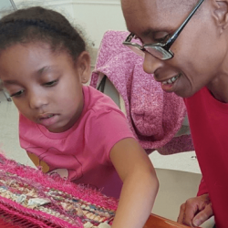 Woman of color and young girl sitting and weaving together