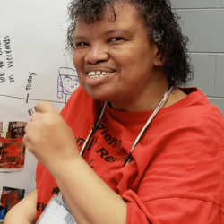 Woman of color sitting in front of a timeline, wearing a red t-shirt and smiling