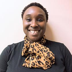 Utibe Akpaninyie-Williams wearing a black top and animal print silk scarf with smiling