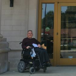 a man sits in an electric wheelchair outside the entrance of a bank with a stone facade